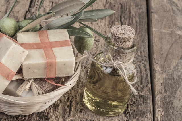 natural soap bars and olive oil bottle on wooden table
