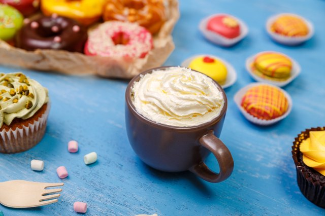 Macaroons, cupcakes and donuts. Mug with cream.
