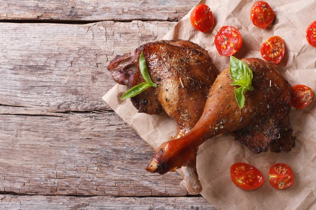 two duck legs with basil and tomatoes