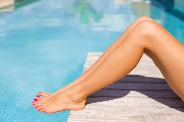 Beautiful tanned women legs by the pool
