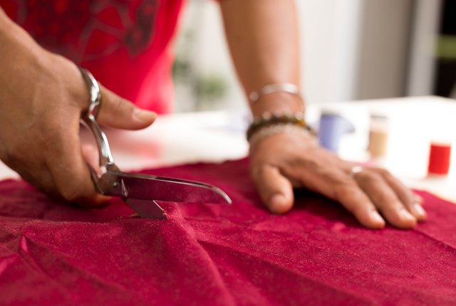 designer working of cutting piece of cloth with scissors
