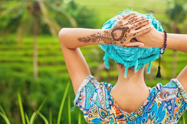 woman with mehendi tatto on her hand in rice field