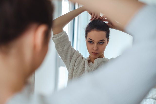 Girl looking in the mirror while making ponytail