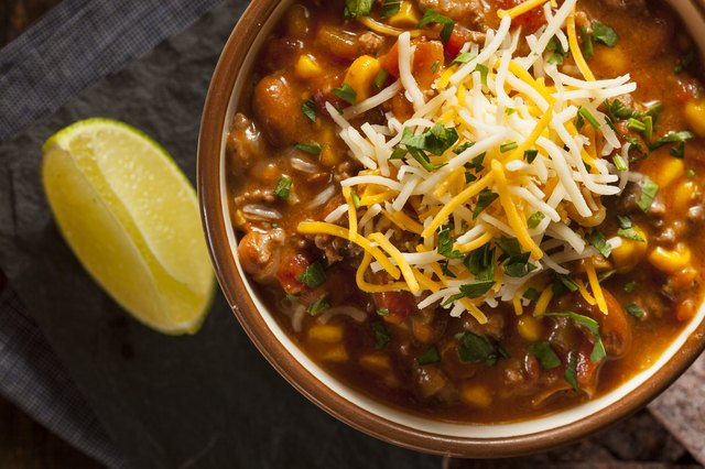Bowl of homemade chili topped with cheese and slice of lemon