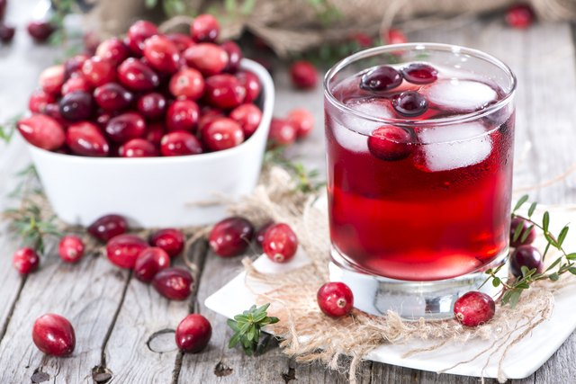 Glass of fresh cranberry juice and a bowl of cranberries