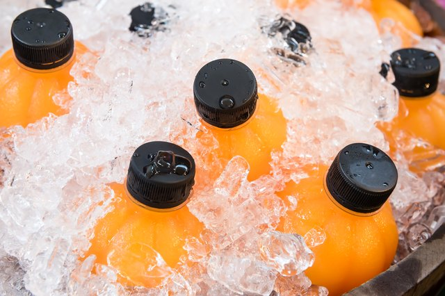 fresh orange juice in plastic bottled in wooden ice bucket