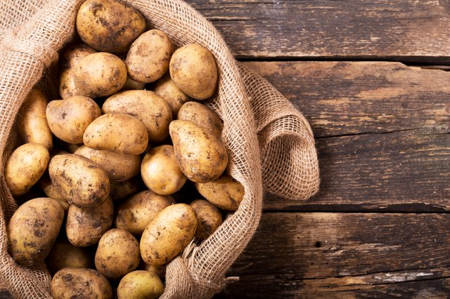 fresh potatoes in sack on wooden table