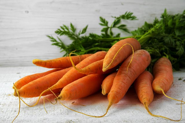 Bunch of fresh carrots with leaves on white rustic wood