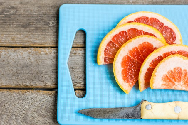 Grapefruit slices  and knife on an aqua  cutting board