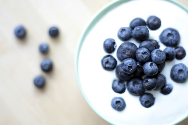 Yogurt with fresh blueberries in a white bowl on a table