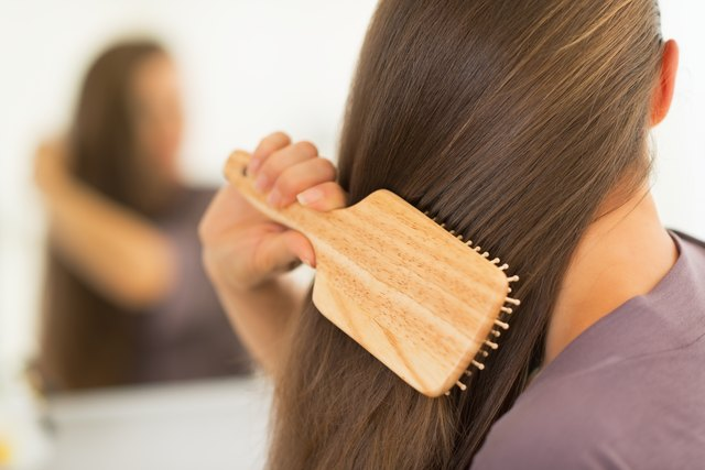 closeup on young woman brushing hair
