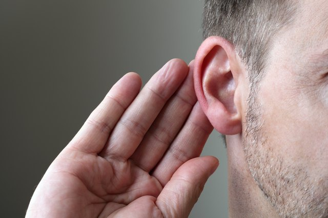 Man feeling behind his ear with fingers