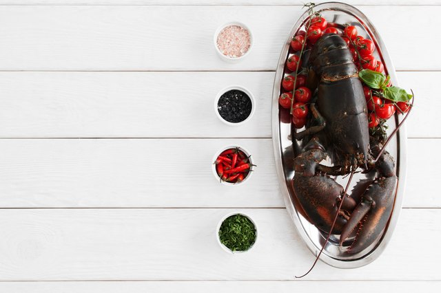 Big raw lobster in plate on table, flat lay