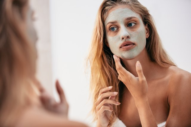 Woman looking in the mirror with face mask