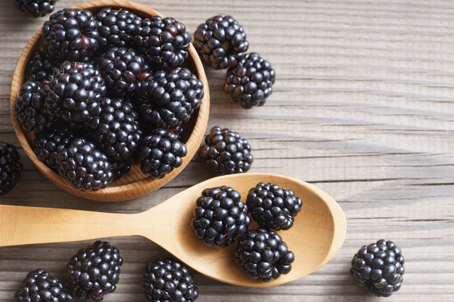 Healthy blackberries in bowl on wooden background.