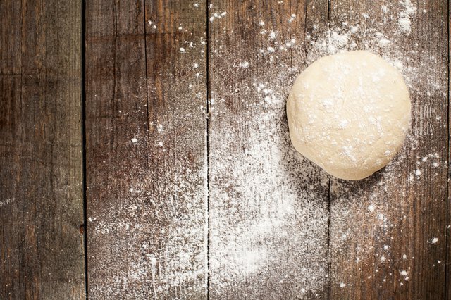 Ball of pizza dough on a rustic wooden background