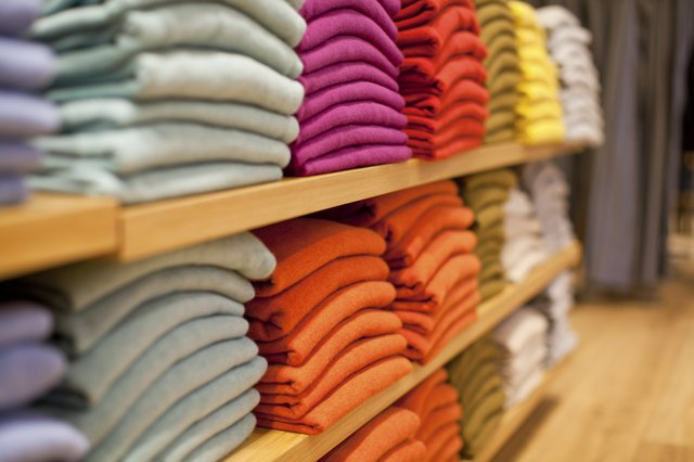 Colorful display of sweaters on shelf in store