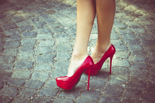 Woman in high heel shoes on an uneven stone path