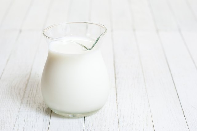 Jug of lactose-free milk on white wood