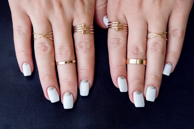 White nail art manicure, hands with fashion gold rings