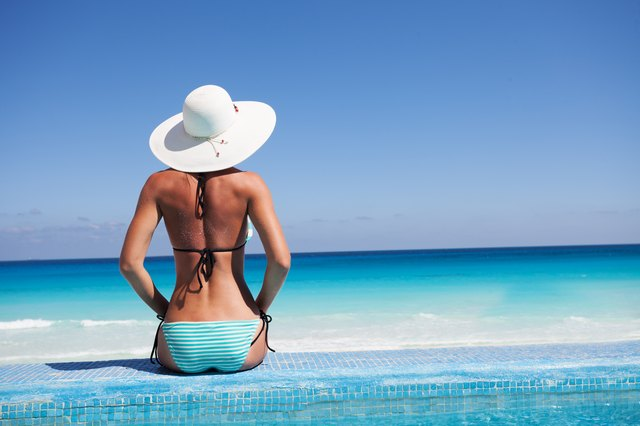 Silhouette of young woman on beach with hat