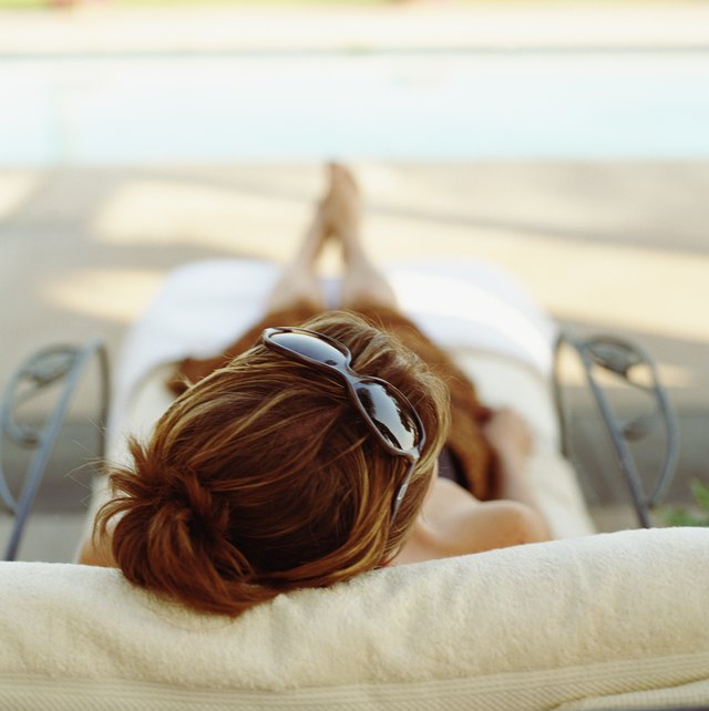 Woman with sunglasses on top of head, lying in lounge chair by pool