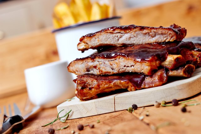Barbecue ribs with fries on rustic wooden table
