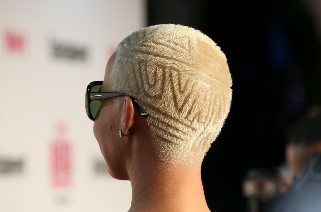 Woman wearing sunglasses with patterns shaved in hair