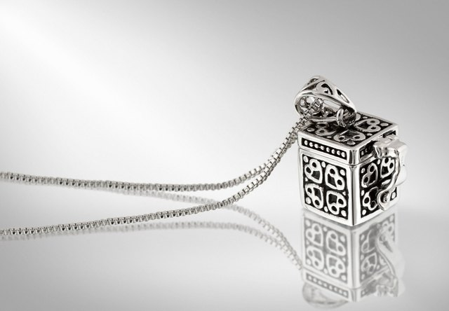 silver pendant with chain on grey background