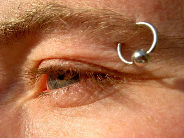 Man with silver eyebrow piercing