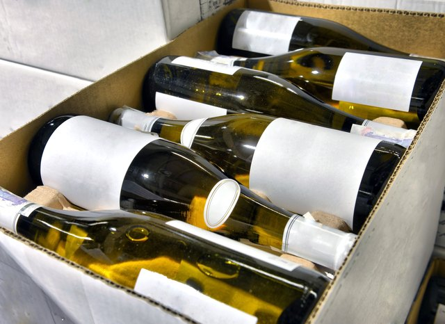 Box filled with unlabeled white wine bottles