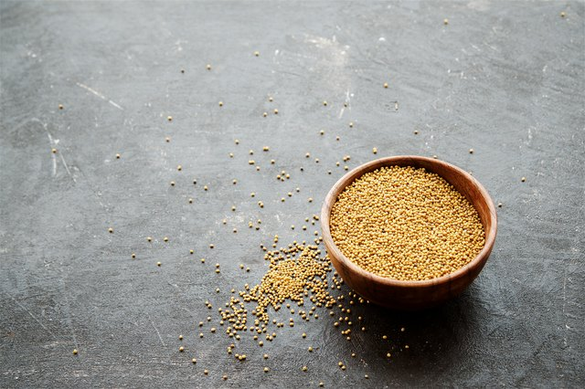Spice mustard seeds in a bowl on a dark background