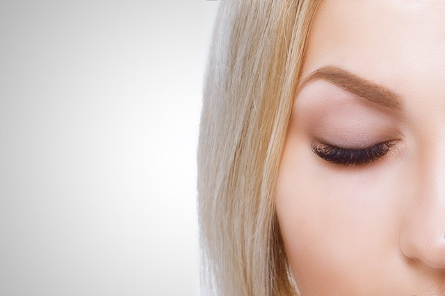 Woman arching her eyebrows with eyes closed