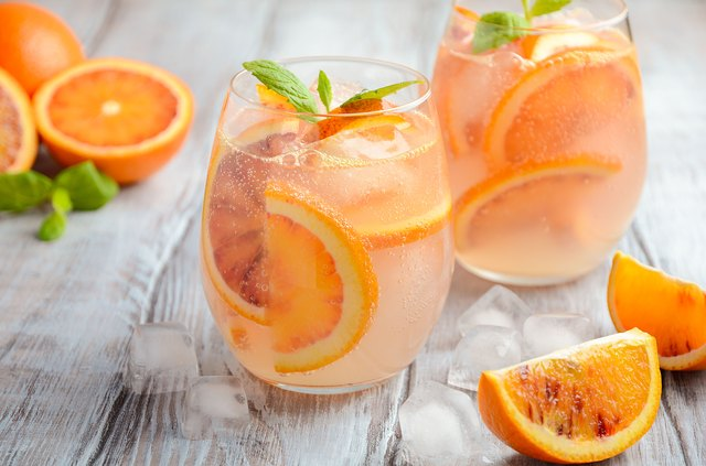 Cold refreshing drink with blood orange slices in a glass on a wooden background.