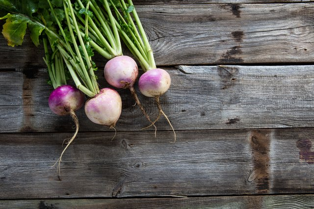imperfect organic turnips, fresh green tops on authentic wood background