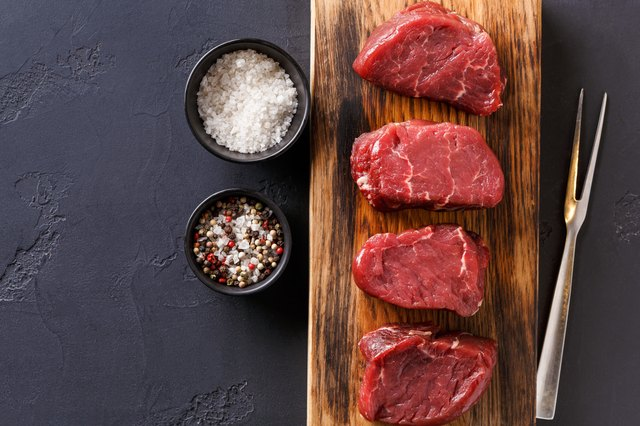 Raw beef filet mignon steaks with spices on wooden board at black background