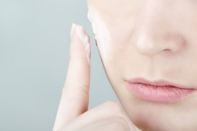 Woman applying skin care cream to cheek