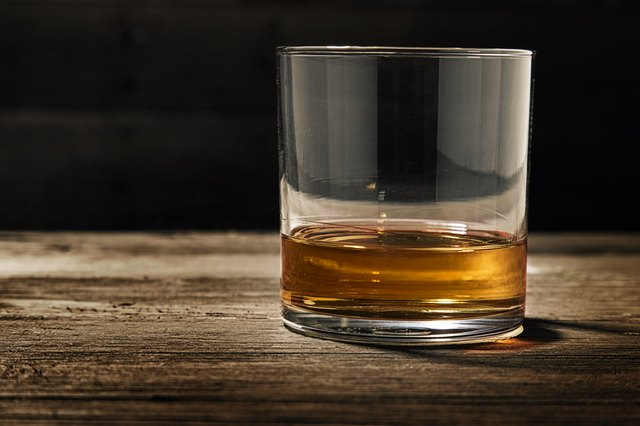 Finger of scotch in a glass on a wooden surface