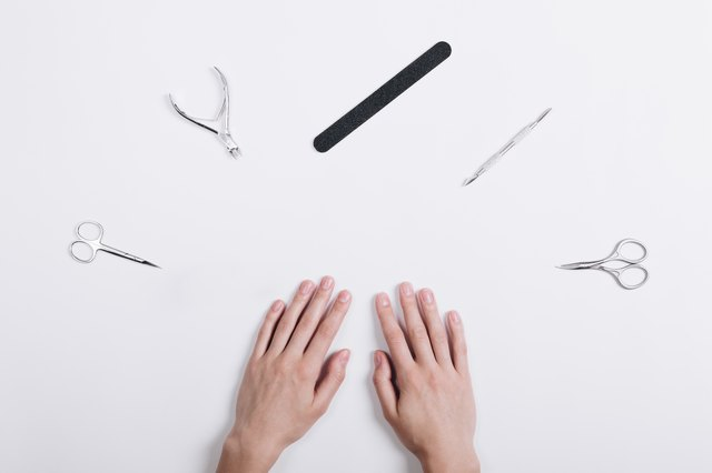 Accessories for manicure lie around a female hands