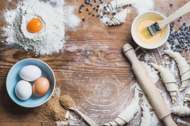 Baking ingredients for cooking croissants over wooden background, copy space
