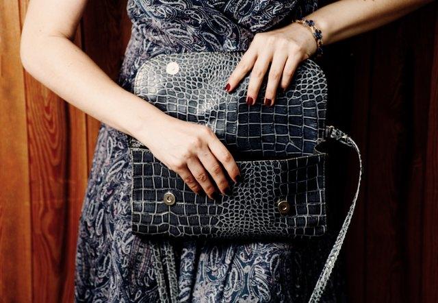 Blue crocodile handbag in hands