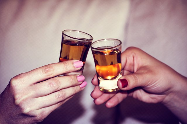 Two woman hands toasting whiskey, brandy with isolated backgroun