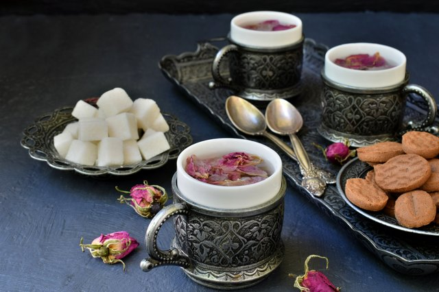 Floral tea made from rose petals and cookies on a dark gray concrete background. Tea drinking in eastern style.
