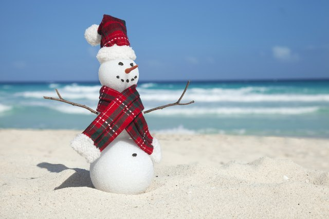 Miniature Snowman Wearing Hat and Scarf on the Beach