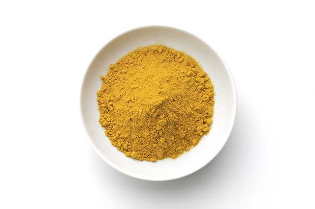 Powdered curcuma in a white bowl on a white background