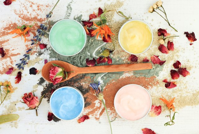 different clay facial masks in jars, powder and dried herbs
