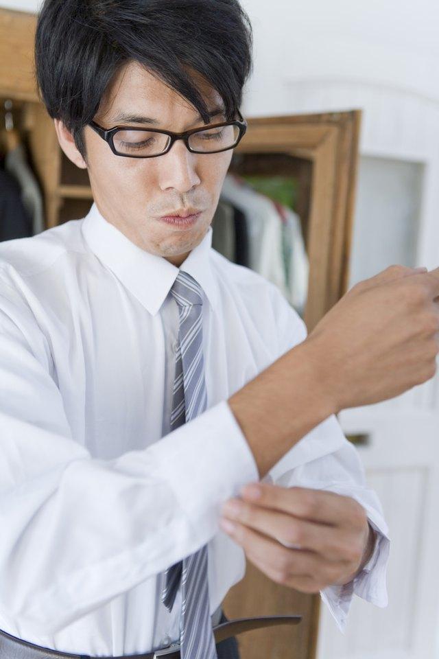 Young man buttoning shirt