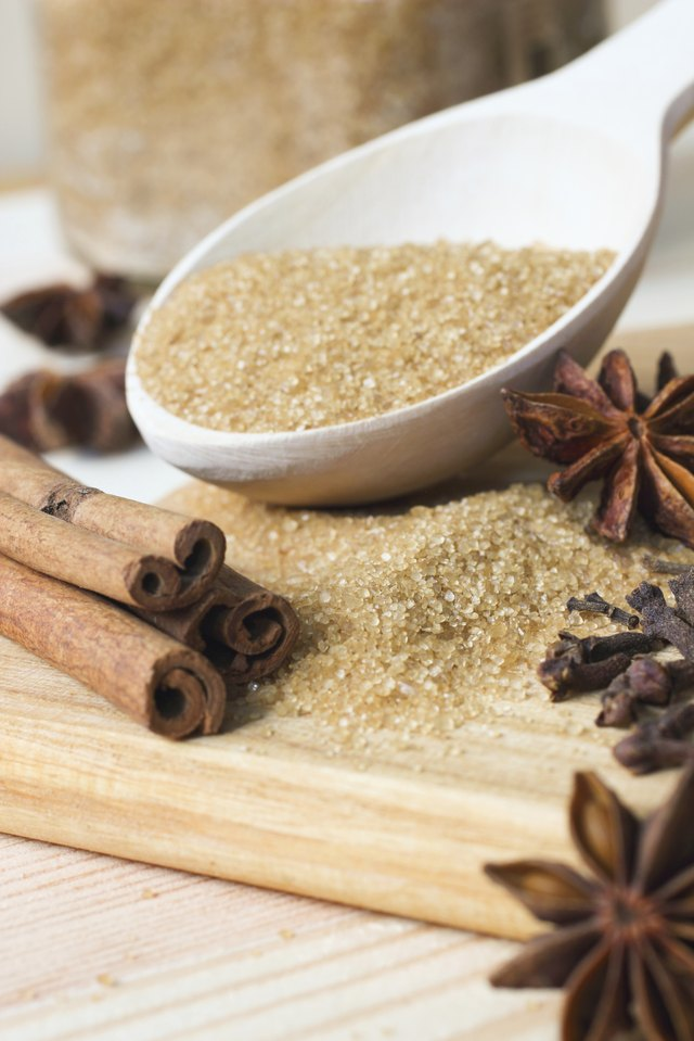 Brown sugar in wooden spoon with spices