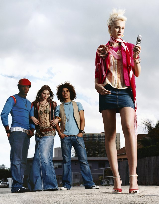 Young Woman Wearing a Mini Skirt and Using a Mobile Phone and Men and Women Wearing Jeans, Out in a City Street