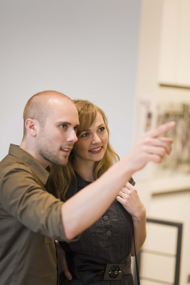 Couple pointing in art gallery
